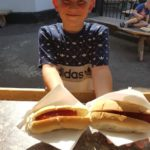 young boy holding hot dogs