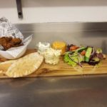 delicious bread and chicken dish served on wooden board